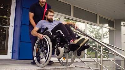 Kierowca pomagający osobie na wózku zejść ze schodów.