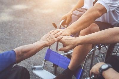 Pomagamy sobie. Trzy ręce się trzymają. Osoby są na wózkach inwalidzkich.